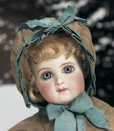 French Bisque Bebe, C EJ, by Jumeau~~~antique costume includes bronze silk hooded capelet, fur muff with blue silk ribbons, silk dress, undergarments, leather shoes. CONDITION; Generally excellent. MARKS: C EJ. COMMENTS: Emile Jumeau, circa 1882. VALUE POINTS: Rare model of EJ is enhanced by superb modelling, pale bisque with delicate blushing, large beautiful eyes with blushing, original body and body finish.