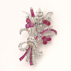 A ruby and diamond brooch in the shape of a bouquet set with numerous circular and square-cut rubies and brilliant, single and old mine-cut diamonds weighing a total of app. 1.70 ct., mounted in platinum. L. app. 5 cm. England, circa 1950.  Estimation : 1.350/1.600€