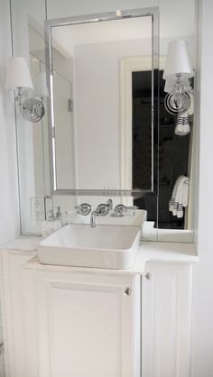 A shaped, stepped back white vanity provides much entry space and and storage. Another trick to making this tiny master bathroom feel bigger is the mirrored wall above the custom vanity. Mirrors work their optical magic by opening up the space and splashing light around the room. | Award Winning White Custom Vanity by Paula McDonald Design & Interiors #bath #bathroom #renovation #vanity