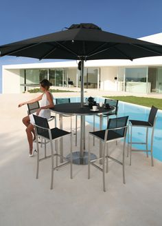 OZON circular exterior bar table, designed by Kris Van Puyvelde for Royal Botania - Belgium. OZON is made with stainless steel frame, in brushed or powder coated aluminium. Table top in toughened glass, ceramic or teak. OZON tables also feature a circular lazy susan. OZON is available in a wide range of sizes and colour finishes.
