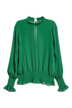 Een blouse van crinklechiffon met lange mouwen en een volantkraagje. De blouse heeft smokwerk en een volant aan de onderkant en onder aan de mouwen en een s
