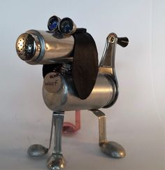 This little pound puppy is waiting for his forever home. What breed of dog is he? You tell me. He is made of a vintage aluminum pepper shaker, a vintage cake decorating tube, a salt shaker top, vintage measuring spoon legs, thimbles with marbles for eyes, and soft black leather ears. His tail is the grating tube from a mouli, that conveniently fits into his salt shaker body. He stands 7 inches tall, and is 8.5 inches tail to nose.