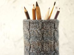Handknitted cozy for a pencil cup or any other small vessel (hint: an empty olive can!).  Traditional cable pattern in browns and greys.