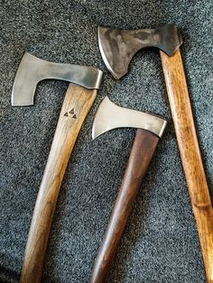 These three Viking style battle axes were re-forged from existing wood axes.They were then re-hardened and tempered and given different aged appearances. The hafts are hickory and again given different aged appearances.