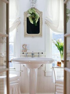 A dramatic and sculptural pedestal sink looks charming in the master bathroom. A bit of fabric and mistletoe for the vintage mirror infuses the room with seasonal color./