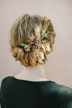Rolled updo adorned with greenery