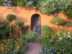 Burnt orange building with blue doorway...beautiful landscaping!