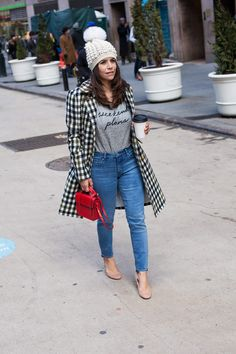The Corporate Catwalk. Grey graphic tee+skinny jeans+blush midi heeled pumps+checked coat+red shoulder bag+white pompom knit beanie. Winter Casual Outfit 2017