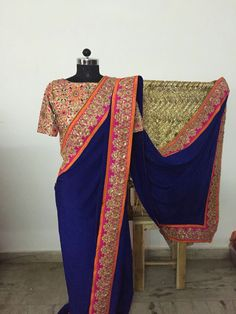 A striking deep blue pure crepe saree with a unique combination of orange and magenta border. The magenta border has intricate golden zari thread work and the finishing is done with golden beads. The heavily embroidered blouse completes the stylish look !!!