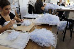 Une dizaine de femmes insèrent avec minutie, une par une, des plumes d'autruche dans du tulle, donnant naissance à la robe bleu ciel qui clôturera un défilé de mode: l'appellation «haute couture» prend tout son sens dans les ateliers Lemarié, plumassier depuis 1880 près de Paris.