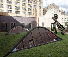 Popping out of the grassy pitch are two skylights channeling light into the art…