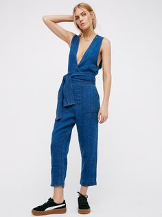 Morning Star One Piece | Linen one piece jumpsuit featuring a plunging surplice neckline with a low V back and dropped armholes. This four-pocket style has an adjustable wrap belt and slouchy cropped legs. Button closure at the back neck.