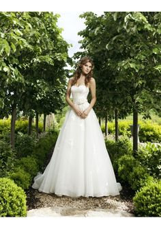This elaborate organza a-line wedding gown features strapless sweetheart neckline, elegant applique accents,rouched waistline adorned with adorable flower and skirt with chapel train. Please be kindly informed that this dress cost excludes any accessories like petticoats, gloves, veils, jackets, crowns, necklaces and so on.