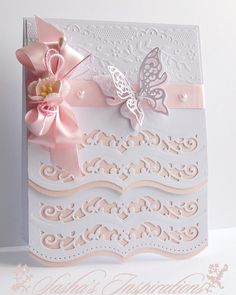 Beautiful card! Spellbinders A2 Bracket Borders One and Les Papillons Two, with a little embossing. From the Pretty Little Ribbon Shop I used 15mm Pale Pink Satin Ribbon - Pink Cherry Blossom, Pearl Pin and Small Pearl Hearts.