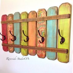 This is a wood coat rack with 5 dark brown metal hat and coat hooks. A cheerful display painted in green, yellow, blues, red and floral then