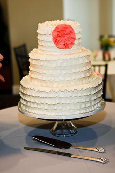 """Bolo de casamento branco com cobertura com efeito """"frufru"""" e flor laranja."""