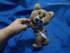 Baby Urso by Litta Santos - modelo 1 <br> <br>Produto 100% artesanal, em feltro, inteiramente cortado e costurado a mão e recheado com plumante siliconado. <br> <br>Ideal para decorar o quartinho de seu bebê ou presentear uma pessoa especial! <br> <br>Pode ser produzido como: <br>- Prendedor de cortinas; <br>- Enfeite para parede ou nicho; <br>- Enfeite para decorar mesa de chá de bebê... <br> <br>Medida aproximada: 24cm de altura. <br> <br>Produto sob encomenda, você pode escolher: <br…