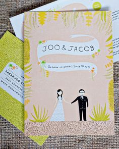 Thesecustom-made cartoon invites from The Indigo Buntingfeatureda color palette of dusty pinks, greens, and browns,an illustrated map, and adouble-sided RSVP card.