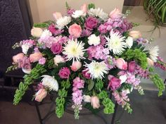 Very feminine casket spray. Filled with Fuji mums, roses and snap dragons.