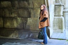 Seventies outfit with flaired jeans and camel cape.