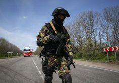 A Ukrainian soldier patrols near a checkpoint outside the city of Slaviansk