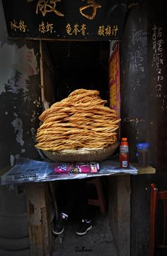 When in Ciqikou Old Town of Chongqing, I saw many interesting things. But this little Micro store selling fried bread was something. If you look closely you can see there is someone behind this mountain of bread who is the seller!!! lol… (via Robert Lio)