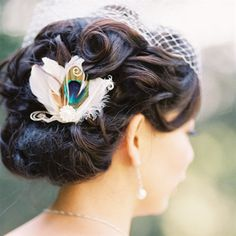 Tianyi wore her hair in a curled updo. For the reception, she traded her cathedral veil for a birdcage veil and added a peacock-feather hairpiece. from the album: A Whimsical Wedding in Pasadena, CA