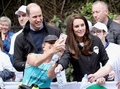 Kate Middleton Photos Photos - A runner takes a photo of Prince William, Duke of Cambridge and Catherine, Duchess of Cambridge as they hand out water to runners during the 2017 Virgin Money London Marathon on April 23, 2017 in London, England. The Duke and Duchess of Cambridge and Prince Harry, are spearheading Heads Together, in partnership with eight leading mental health charities, that are tackling stigma, raising awareness, and providing vital help for people with mental health…