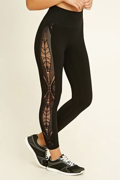 A pair of seamless capri leggings featuring ornate cutout patterns on the sides, an elasticized waist, and moisture management.