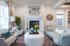 Project Miller Ave Formal Living Room | ML Interiors Group | Dallas, Texas | Round Ottoman Coffee Table | Blue Tufted Sofa | Custom Upholstered Heirloom Chairs | Abstract Art | Yellow Tulips | Fiddle Leaf Fig Tree | Floral Curtains