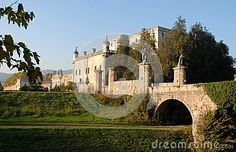 Photo made at the castle Catajo in the province of Padua in Veneto (Italy). In the picture, made at first autumn afternoon, we see a detail of the bridge, with the two large statues, which connects the road to the courtyard of the massive central body of which one sees the side facing south. It also sees the walls located opposite the castle that goes on in the distance as the castle lit by the sun and immersed in greenery and dominated by the blue sky.