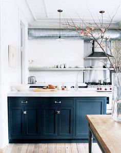 A light and airy modern vintage kitchen featuring white walls, exposed duct work, open shelves, dark gray lower cabinets, pale bleached wood floors and a rustic wood farm table -  Modern Vintage Kitchen Ideas & Decor