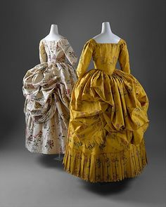 "Robes à la Polonaise (1780-85) made of silk de chine with hand-painted multicolored floral sprays  ""The polonaise gown first came into fashion in the 1770s. It was a style of gown with a close-fitting bodice and the back of the skirt gathered up into three separate puffed sections to reveal the petticoat below. The method of suspending the fabric varied. Most often the dress had rows of little rings sewn inside the skirt through which a cord ran from hem to waist. Alternatively, r..."