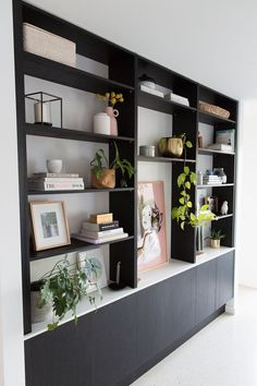 How to: Style a bookshelf. Black bookshelf styled in a modern way with blush pink decor, brass accents, indoor plants, and other homewares. Find all the tips and tricks to style a bookshelf like a pro.