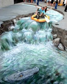 This art piece shows how realistic the drawing on the floor is by the water rushing down the rocks and the kids on the raft.
