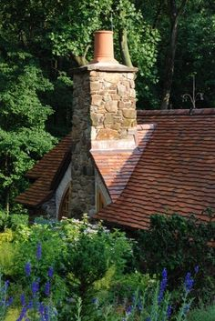 French clay tile roof is lovely on this hobbit house.  Mixes nice with the stone chimney stack!