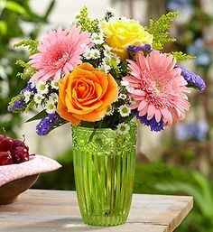 This tumbler vase comes filled with brilliant yellow and orange roses, pink Gerberas and yellow solidago!