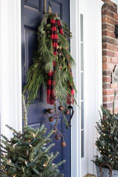 This brilliantly simple door decor fromOn Sutton Place features fresh pine bunches in lieu of a wreath, accented with a plaid scarf and string of bells.