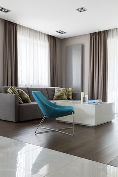 Colourful modern living room, turquoise armchair, white coffee table, grey living room, grey sofa, grey curtains