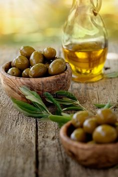 Fresh olives and olive oil on rustic wooden background Olives in olive wood   | Photographer: Nikkiphoto #123RF