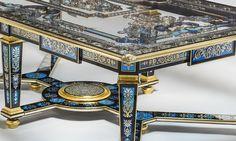 L'entretoise et les pieds, la ceinture et le plateau, sont entièrement réalisés en marqueterie de laiton et d'étain incrustée dans du verre teinté
