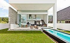 Casa minimalista elimina parede entre sala e piscina
