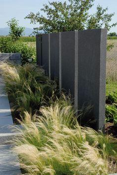 Anthrazitfarbene Stelen bilden den ruhigen Hintergrund für die Gräser, die im feinen Luftzug des Windes wehen. Ein echter Blickfang, bevor das Auge sich in schöner Landschaft verliert. Gleichzeitig verdecken sie die Aussicht auf die Arbeit, die im Gemüsebeet wartet.