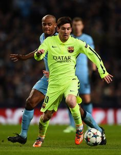 Lionel Messi of Barcelona skips past Vincent Kompany of Manchester City during the UEFA Champions League Round of 16 match between Manchester City and Barcelona at Etihad Stadium on February 24, 2015 in Manchester, United Kingdom.