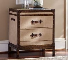 "Redford Trunk Bedside Table #potterybarn  23.5"" w x 18"" d x 26.25"" h Handcrafted with a kiln-dried solid hardwood frame and steel base. Wrapped in tea-stained finish natural burlap with metal trim, brass nailheads and leather handles. Table top has a multistep natural finish; steel legs have a matte bronze finish. Simple assembly."