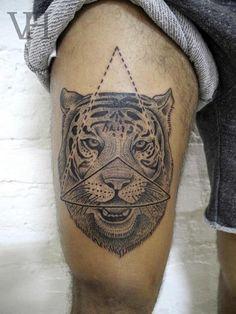 Tatuaje de la cabeza de un tigre con un triángulo a su alrededor.