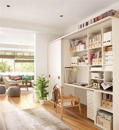 Estudio con mueble con escritorio, estanterías y armario integrados en blanco, silla de madera y fibra, cajas, archivadores, libros y con el salón al fondo con pufs y mesitas auxiliares redondas
