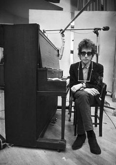 """Bob Dylan At Piano During Recording Session, 1965. Bob Dylan in a contemplative mood, lost in thought behind his Ray-Bans, pausing for a break between takes at the upright piano at Studio A, Columbia Recording Studios in New York City during the sessions for """"Highway 61 Revisited"""" in June 1965, a mere month before his electric set at the Newport Folk Festival would send Folk and Rock and Pop music into a whole new direction. –Photo by Jerry Schatzberg"""