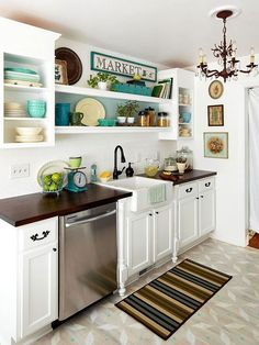 In a one-wall kitchen, open upper cabinets help the room feel spacious and allow space for displaying colorful dishware, potted herbs, and accessories.