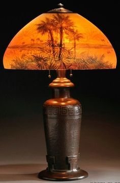 lighting, Connecticut, Handel reverse painted table lamp, glass and patinated metal, Meriden, Connecticut. Domed shade reverse painted with desert landscape of palm trees on a yellow shaded to orange ground, over three socket cluster with acorn pulls and patinated metal vasiform base with geometric bands on a textured surface, shade interior marked Handel 6310 and signed F.V., shade rim impressed with Handel Lamps, base marked Handel. Circa 1916-1925